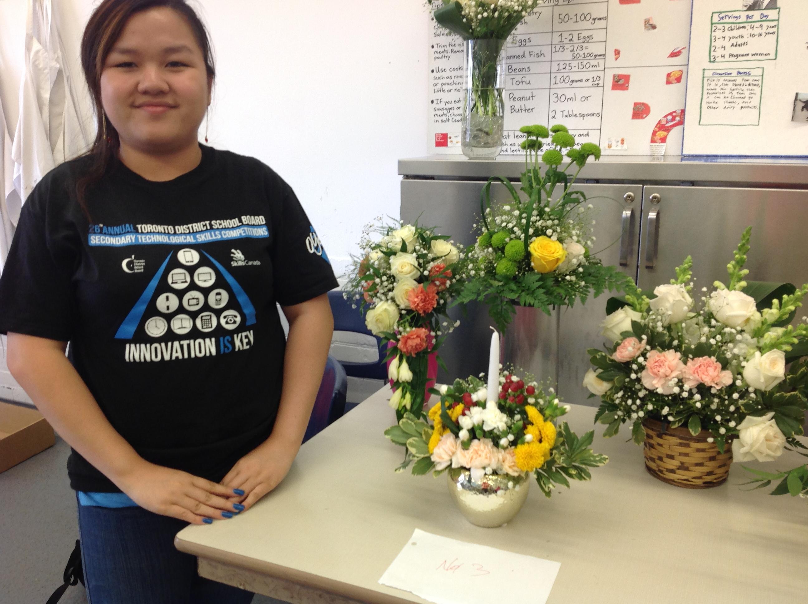 student beside floral arrangements