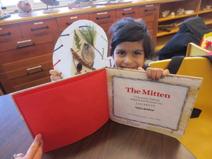 Student holding the book The Mitten holding artwork