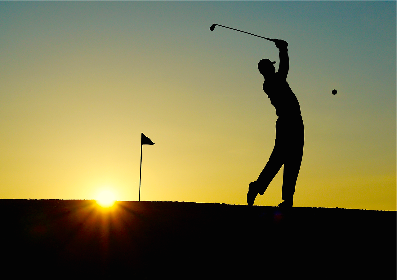 Golfer playing in the sunset
