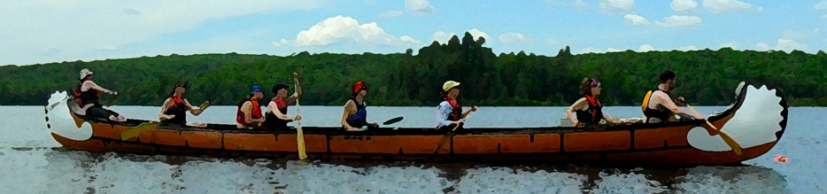 Large voyageur canoe with many people paddling at SOES.
