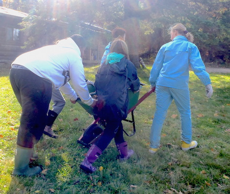 Students working together to move a wheelbarrow of wood chips for repairing a trail