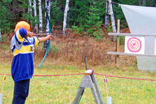 Boy holding a bow and arrow shooting at a target