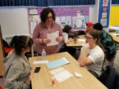 Two students helped by their English teacher