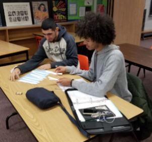 Two English students working on unscrambling a paragraph