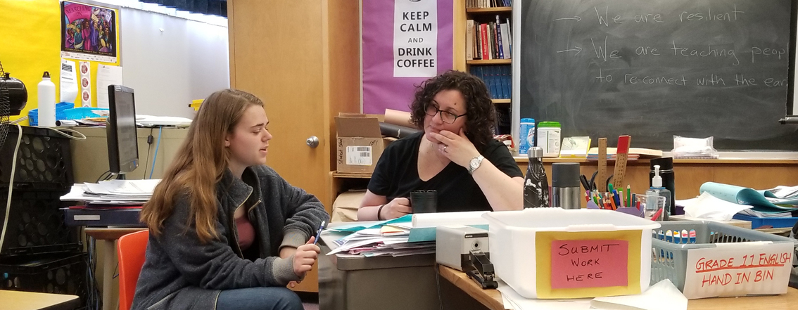 Student reviewing essay organizer with her English teacher